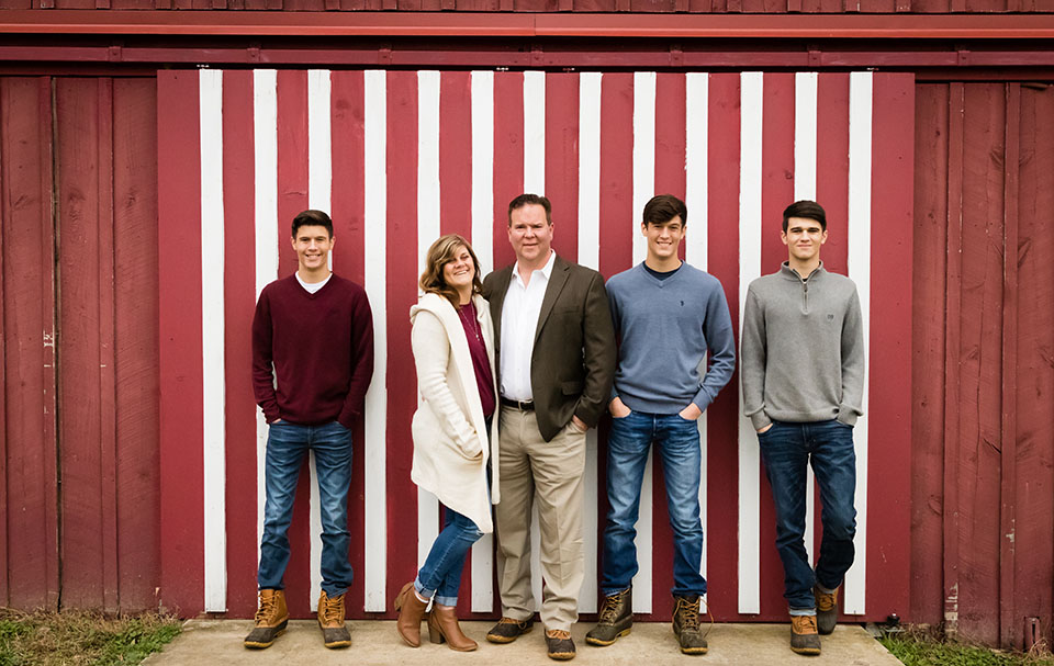 Family photo in front of red and white striped barn door, Valley View Farm